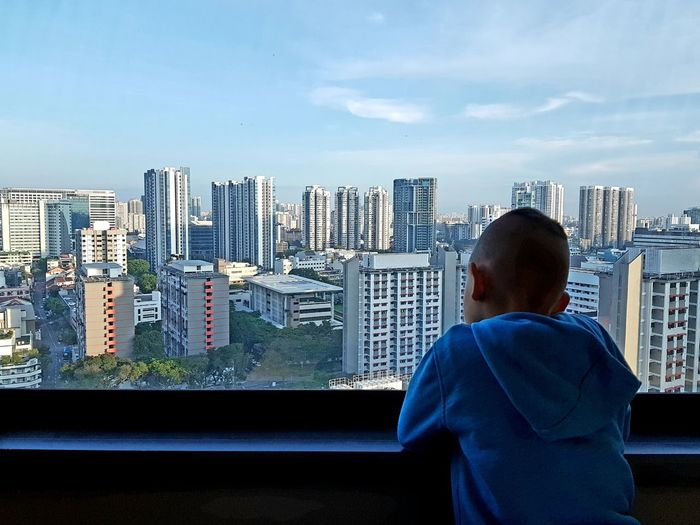 Rear view of boy standing by window with buildings in city against sky