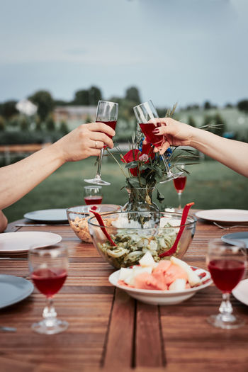 Couple making toast during summer outdoor dinner in a home garden. hands holding classes with wine
