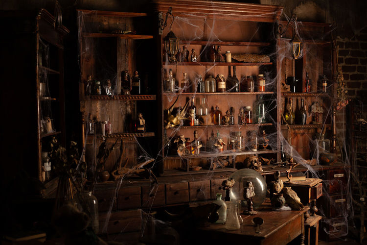 Bottles on shelf with spider web