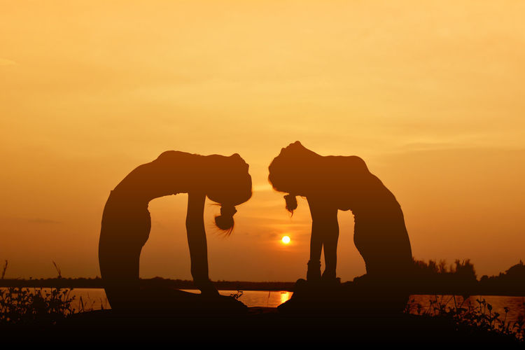 Silhouette Of Women Doing Yoga Against Sky During Sunset