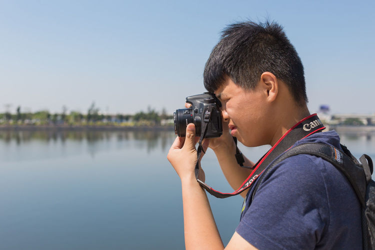 Side view of man photographing against clear sky