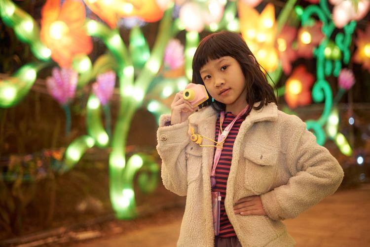 Cute girl standing in illuminated carnival