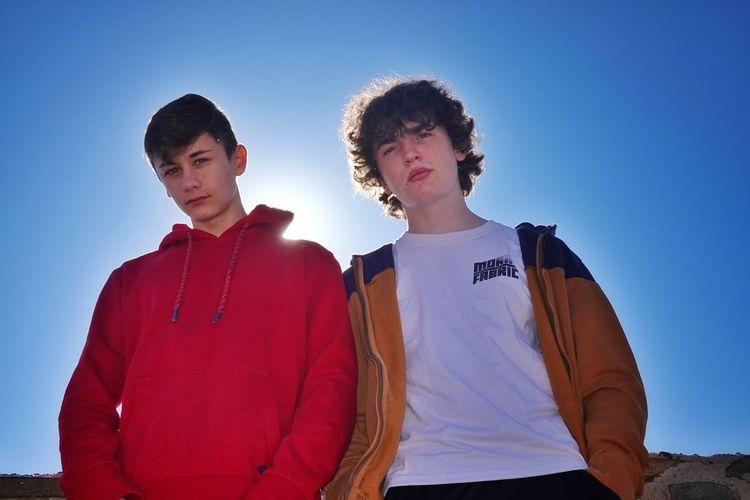 Portrait of teenage boy standing against clear blue sky
