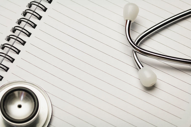 Close-up of stethoscope on spiral notebook
