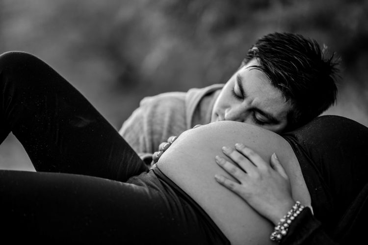 Man sleeping on pregnant woman stomach in park