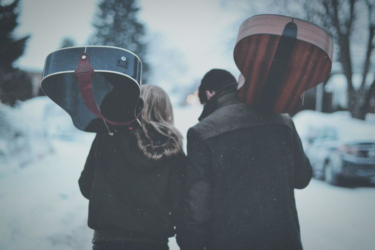 Rear view of friends walking with guitar walking during snowfall