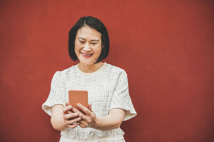 Asian woman using smartphone Communication Smiling Wireless Technology Mobile Phone Technology Happiness Connection Emotion Smart Phone One Person Red Casual Clothing Asian  ASIA Japan China
