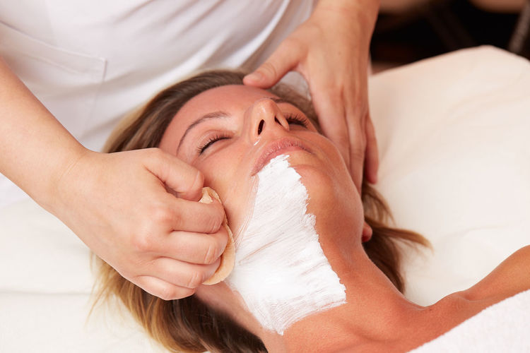 Midsection of beautician cleaning customer facial mask in spa