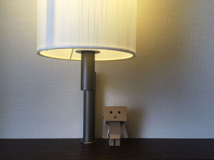 Close-up of electric lamp by figurine on table against wall at home