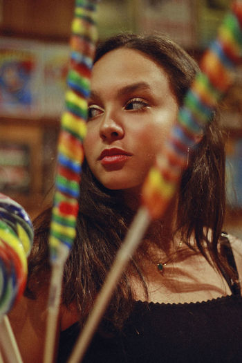 Lollipop, 2018 Candy Store Beautiful Woman Candy Child Contemplation Focus On Foreground Hair Hairstyle Headshot Indoors  Innocence Leisure Activity Lifestyles Lollipop Long Hair Looking Looking Away Multi Colored One Person Portrait Rainbow Real People Women Young Adult Young Women The Portraitist - 2018 EyeEm Awards