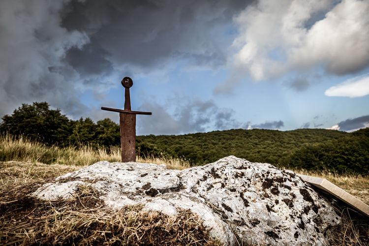 Cross on rock against sky
