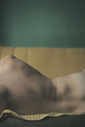 Midsection rear view of shirtless man sleeping on sofa at home