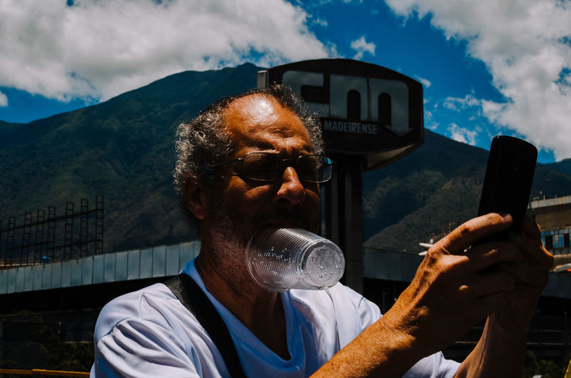 Portrait of man holding camera against mountain