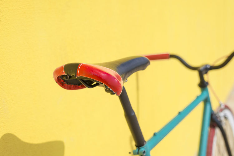 Close-Up Of Bicycle Against Yellow Wall