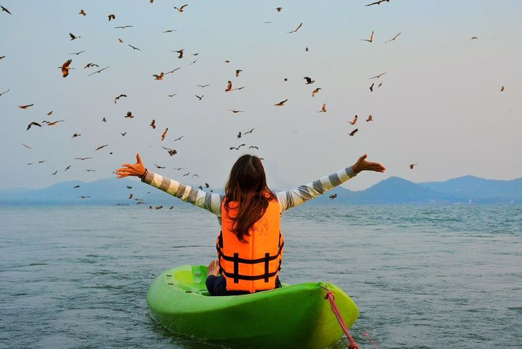 Rear View Of Woman With Arms Outstretched While Kayaking On Sea Against Birds In Sky