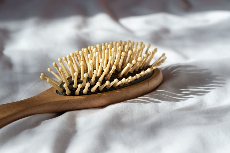 Close-up of hair brush on bed