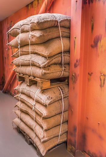 Stacked sacks by wall at warehouse