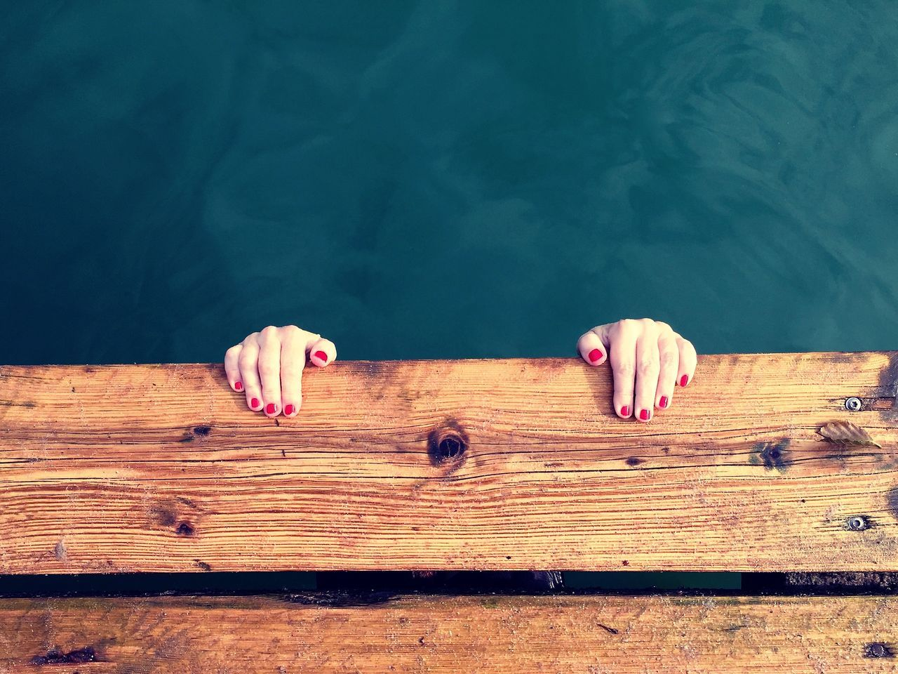 Cropped image of woman hanging on jetty over lake