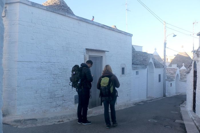 Alberobello Alberobello - Puglia Alberobelloexperience UNESCO World Heritage Site Architecture Building Exterior Built Structure Day Full Length Headwear Lifestyles Men Outdoors People Real People Rear View Sky Standing Two People Warm Clothing Women Young Adult