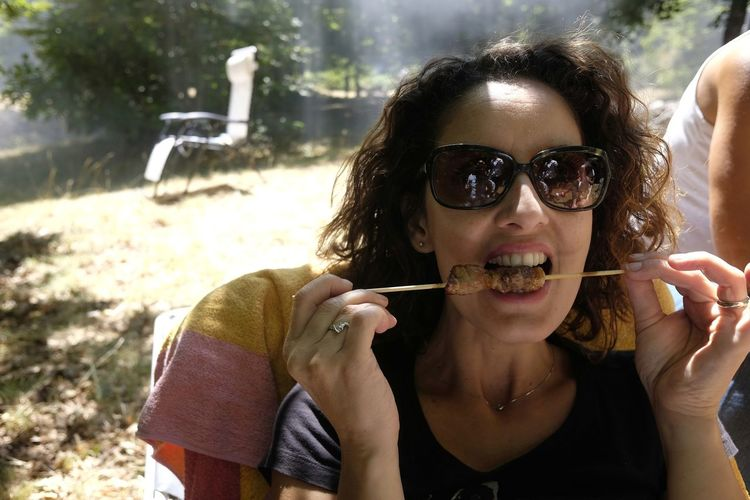 Woman eating arrosticini on field during sunny day