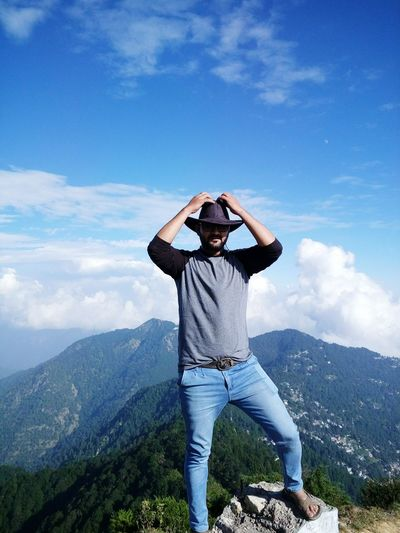 Man wearing hat while standing on rock against mountain