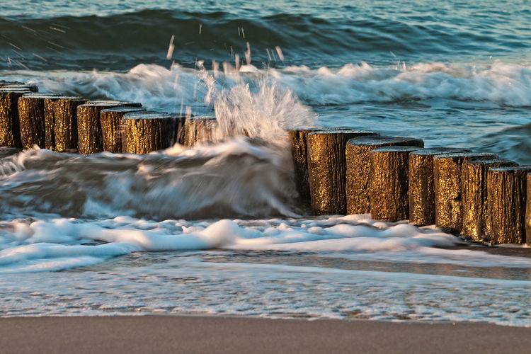 Waves splashing wooden post in sea