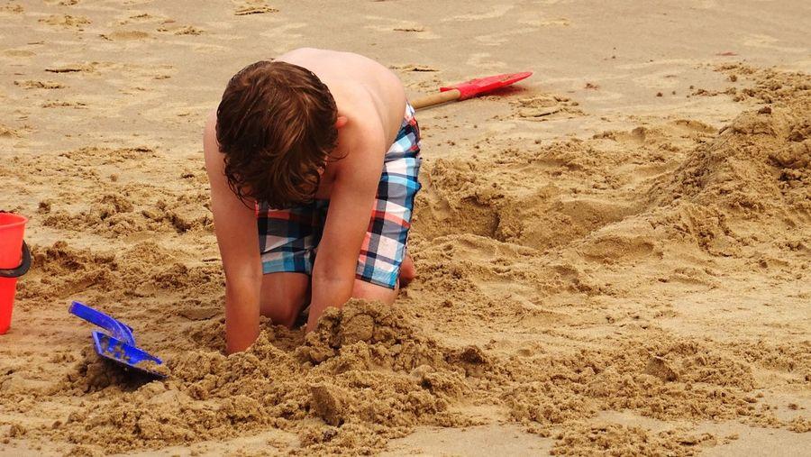 Shirtless Boy Digging Sand At Beach