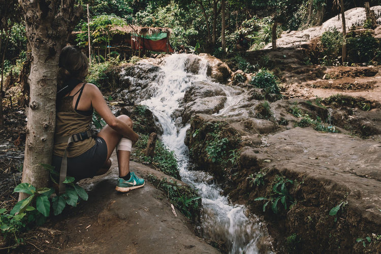 A girl kneels beside a river looking at a waterfall with a leg injury. - IG @LostBoyMemoirs (Photos taken on Canon 650D Rebel T4i, edited in Lightroom.) People People Watching People Photography Streetwise Photography Street Photography ASIA Myanmar Burma Myanmar Culture Myanmarphotos Adventure Backpacking Culture And Tradition Cultures Exploration Travel Destinations Real People One Person Motion Plant Waterfall Water Flowing Water Nature Full Length Lifestyles Leisure Activity Long Exposure Forest Tree Scenics - Nature Beauty In Nature Blurred Motion Day Flowing Outdoors International Women's Day 2019 The Art Of Street Photography
