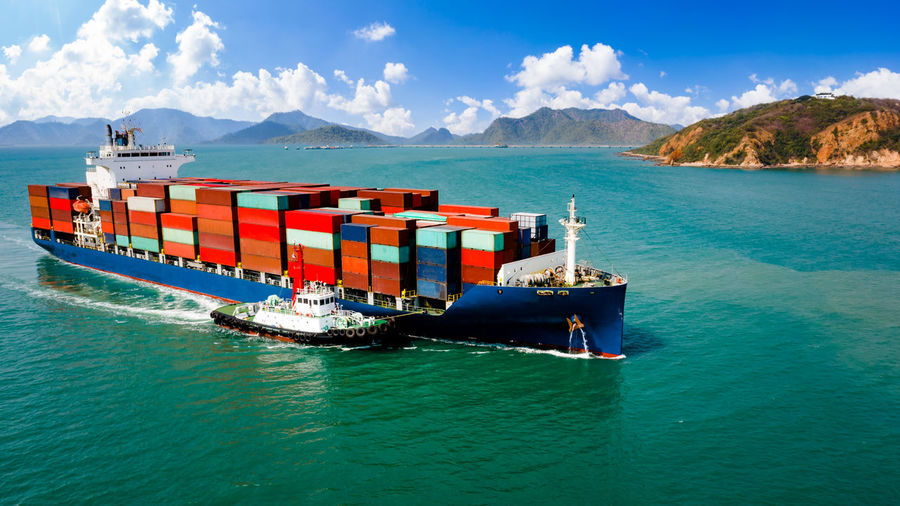 Containers ship and tugboat sailing open sea and mountain background business