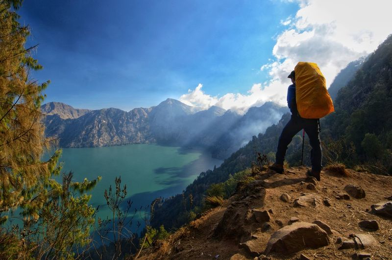 Hiker man with backpack standing, enjoy and happy with active volcano Baru Jari, Lake Segara anak and summit of Mount Rinjani view after finished climbing at Rinjani Mountain, Lombok indonesia. Sunset Sky And Clouds Amazing View Nature Sunrise Rinjani National Park Senaru Landscape Ilovephotography Ilovenature Wallpaper Rocks And Water Backpacking Lombok INDONESIA Base Camp Blue Sky Travel Water Tree Mountain Full Length Adventure Lake Women Standing Hiking Sky Volcanic Landscape Volcanic Rock Hiker Mountain Peak Geology Volcano Active Volcano The Natural World