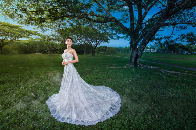 Wedding Dress Fashion,Model wearing a white wedding dress in lawn. Beautiful Married The Fashion Photographer - 2018 EyeEm Awards Beautiful Woman Beauty Bride Clothing Dress Fashion Field Garden Grass Leisure Activity Luxury Model Nature Newlywed One Person Outdoors Portrait Tree Wedding Wedding Dress Women Young Adult The Portraitist - 2018 EyeEm Awards