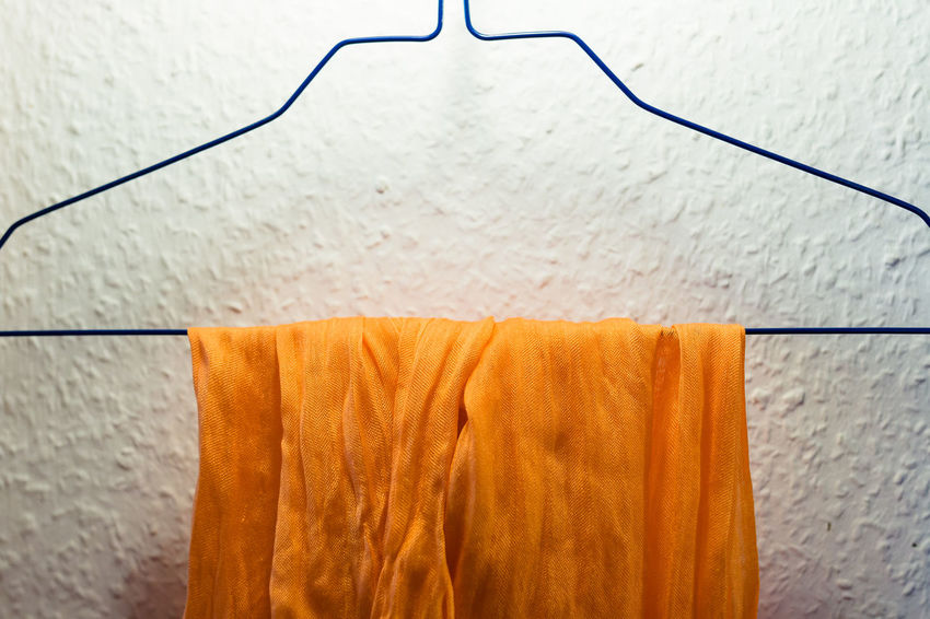 An orange scarf is hanging on a blue coathanger. Architecture Built Structure Close-up Cloth Coathanger Day Drying Hanging Indoors  Neon Life No People Nusshain 07 17 Orange Color Pumpkin Pie Color Scarf