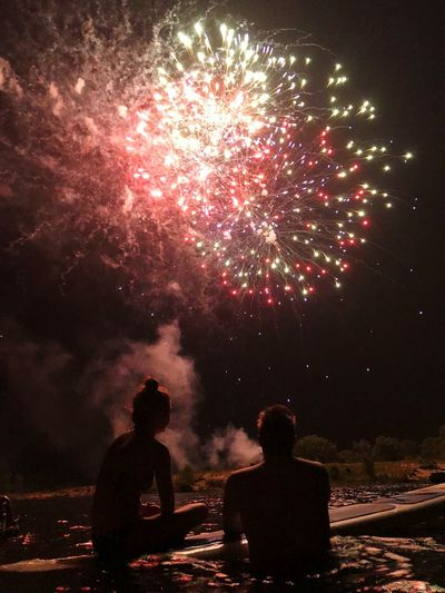 Rear view of people looking at firework display at night