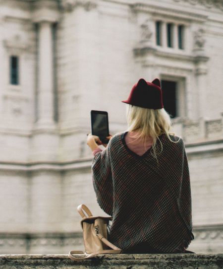 Woman photographing with mobile phone in city