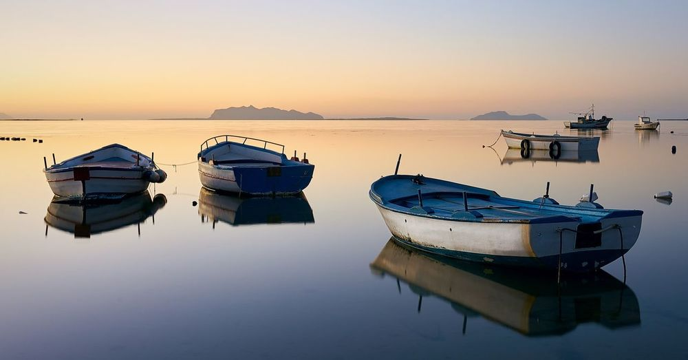 Boats moored in sea against clear sky at sunset