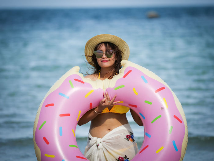 Portrait Of Woman Holding Donut Pattern Inflatable Ring At Beach