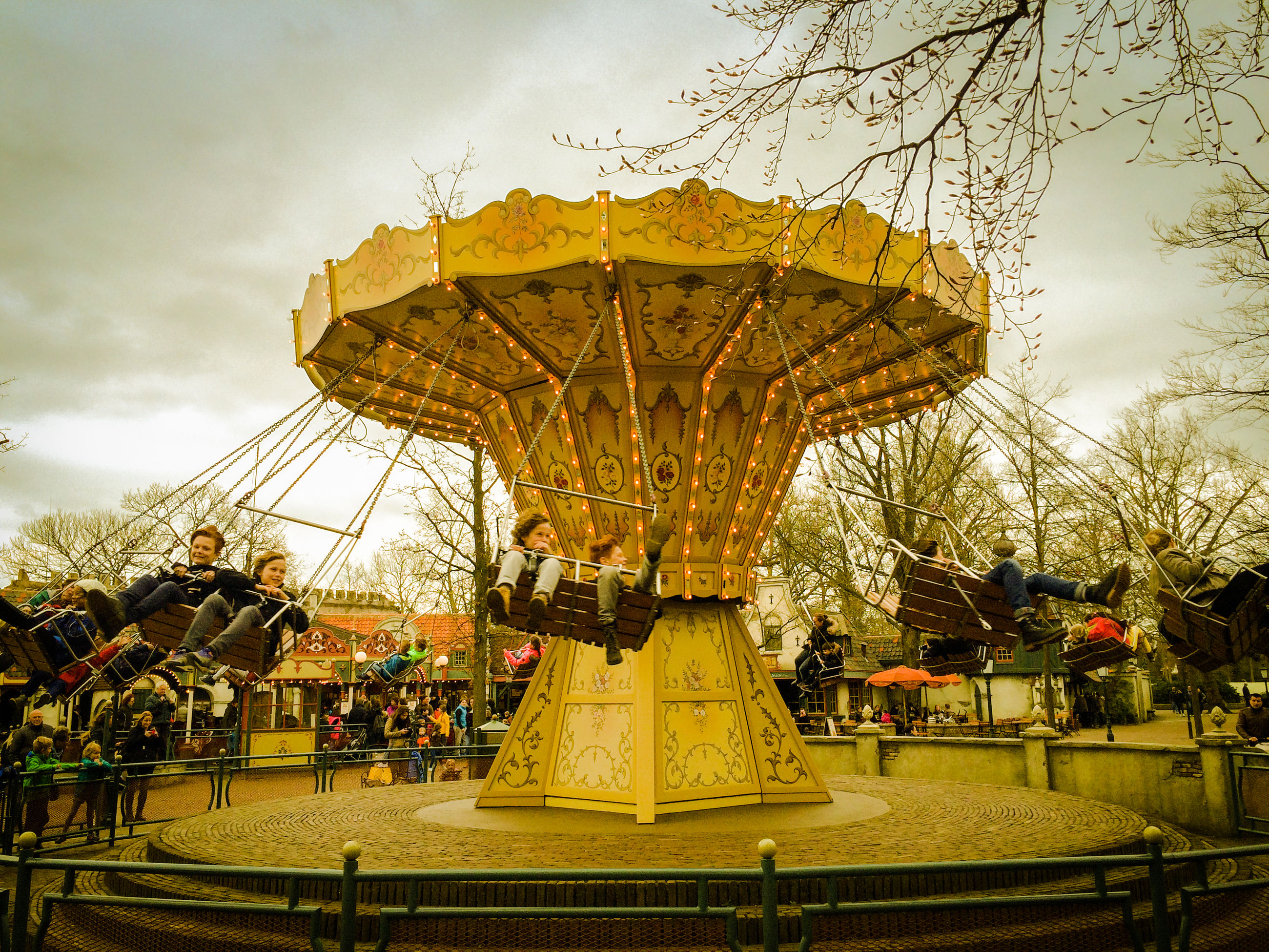 amusement park, arts culture and entertainment, amusement park ride, fairground ride, carousel, leisure activity, enjoyment, sky, cloud - sky, merry-go-round, large group of people, fun, carousel horses, outdoors, day, real people, tree, people