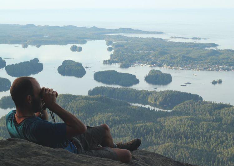 Man looking at lake through binoculars while relaxing on cliff