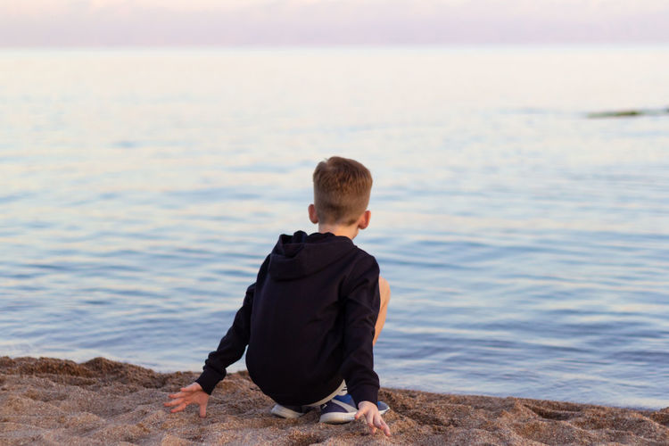 Rear view of boy crouching at beach