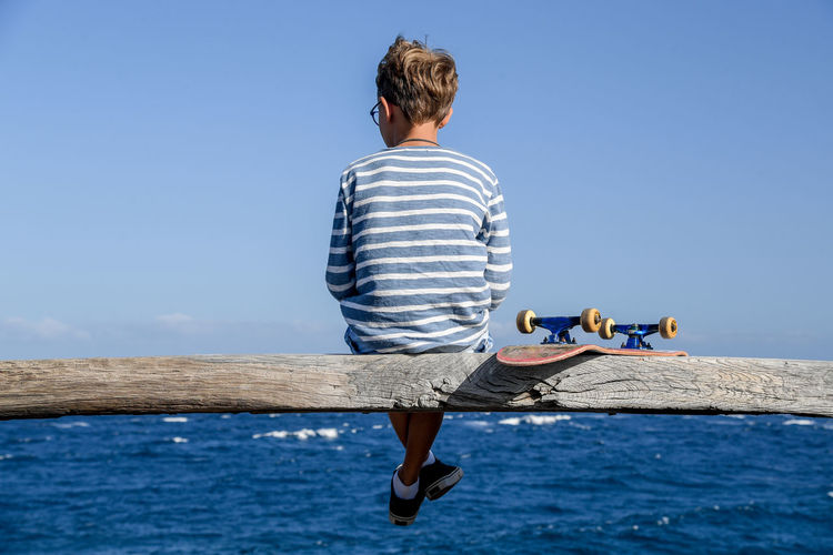 Rear view of boy sitting on wooden log over sea against clear blue sky
