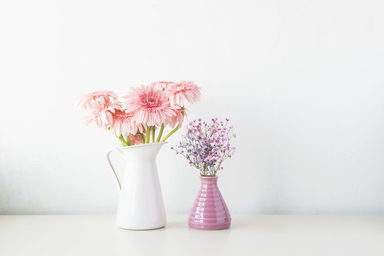 Beauty In Nature Bunch Of Flowers Close-up Container Copy Space Flower Flower Arrangement Flower Head Flowering Plant Fragility Freshness Indoors  Inflorescence Nature No People Petal Pink Color Pitcher - Jug Plant Still Life Table Vase Vulnerability