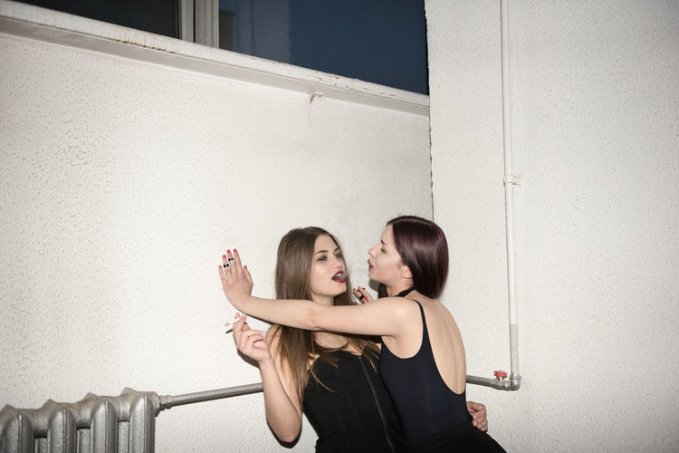Lesbian couple smoking cigarette against wall