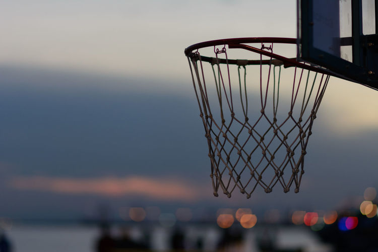 Close-up of basketball hoop against sky during sunset