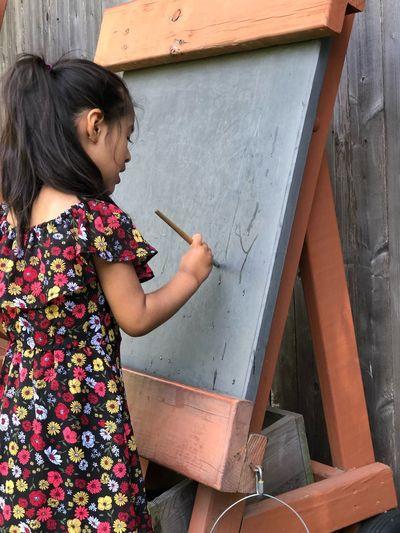 Girl Holding Paintbrush On Blackboard