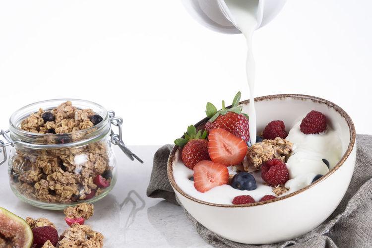 Granola with berries, milk and yoghurt Berries Cereal Bowl Of Cereal Breakfast Granola Granola With Berries Granola With Fruit Healthy Breakfast Healthy Eating