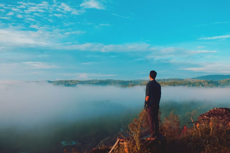 Full length of man looking at mountains while standing against sky during foggy weather