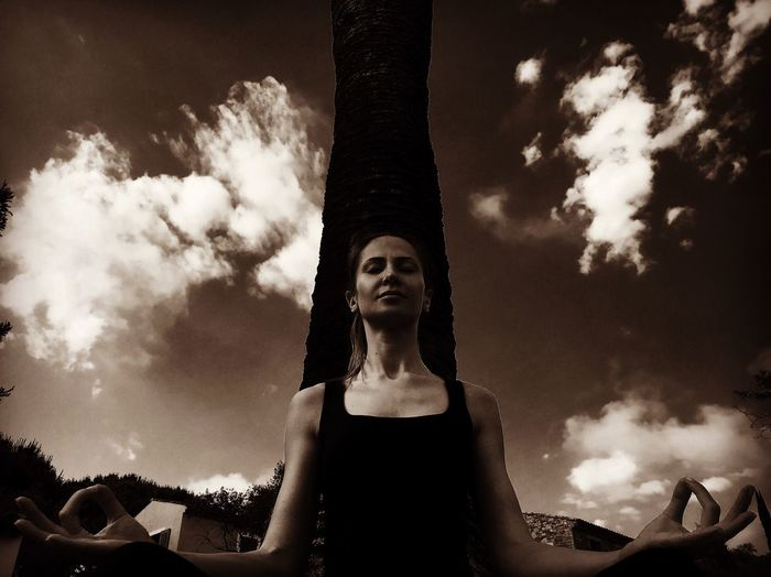 Low angle view of woman meditating in yard against sky