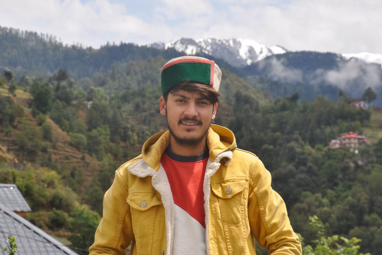 A north indian young men standing outdoor against beautiful mountains.