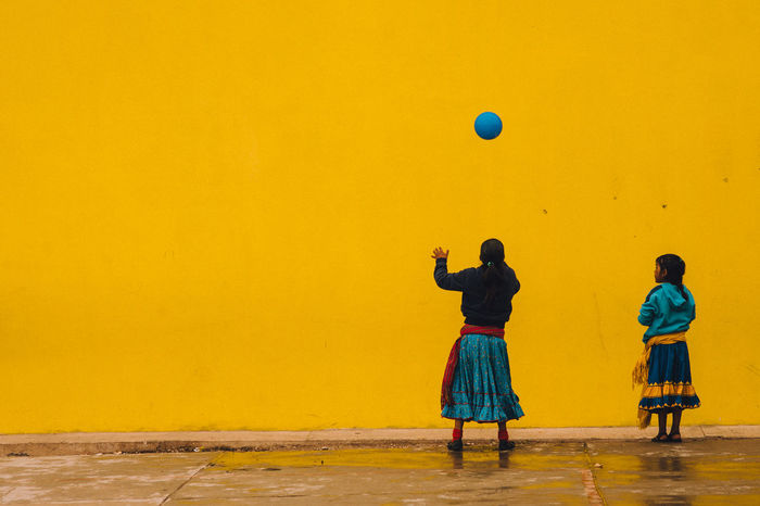 Tarahumara girls playing Mexico Paint The Town Yellow Sierra Tarahumara Ball Blue Childhood Girl Outdoors People Playing Real People Tarahumara Two People Yellow