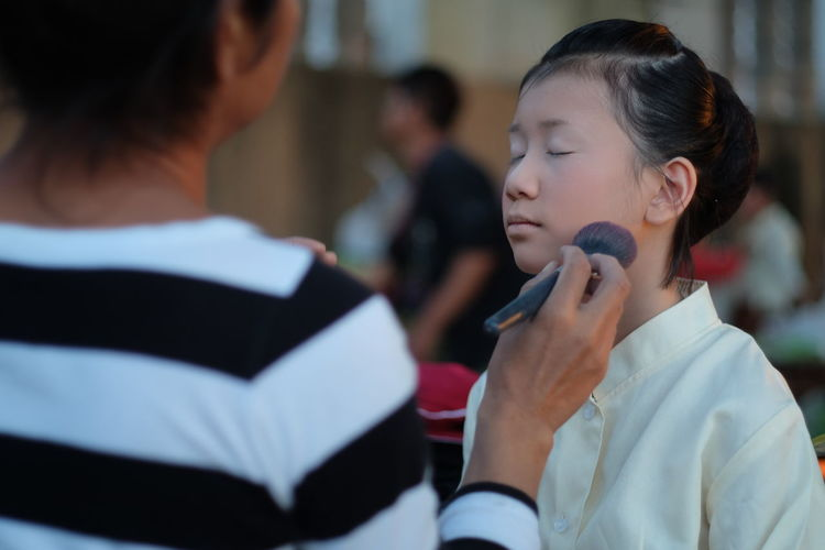Artist make up artist applying make-up with brush on girl